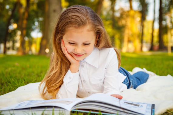 Pretty little girl reading book in park. Education concept