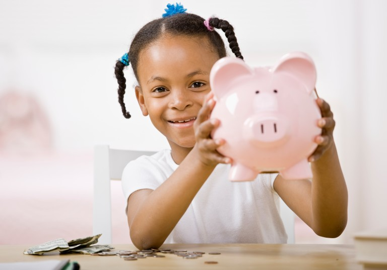 Little girl holding a piggy bank.